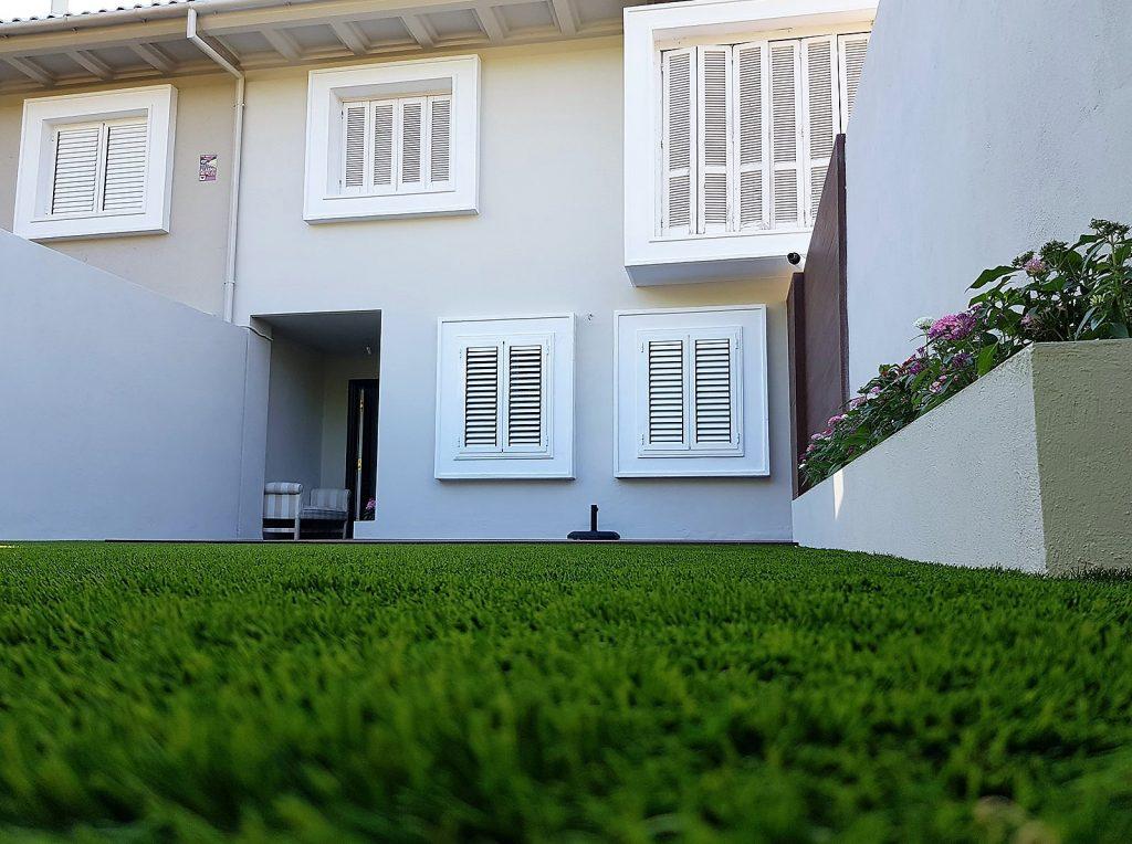 Vistar del cerped verde y ventanas blancas de la reforma de la vivienda unifamiliar
